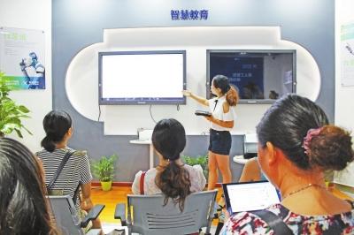 鄢光莉老师正在利用智能设备为小朋友上课本报记者柯雨摄